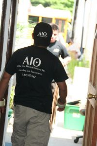 All in One Moving experts with company t-shirts and caps, hard at their relocation work.